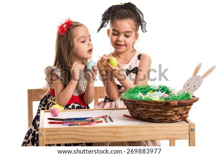 Two little girls painting Easter eggs and sitting together at table isolated on white background - stock photo