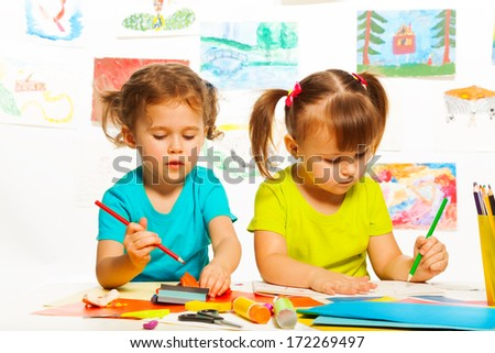 Two little girls painting on creative class in kindergarten - stock photo