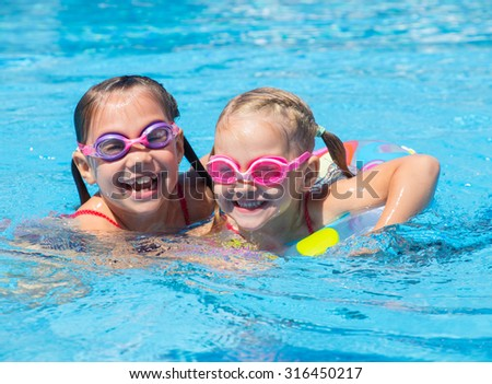 Two little girls play and swim in the pool - stock photo