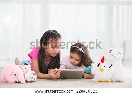 Two little girls playing with a tablet computer  - stock photo