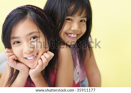two little girls posing to camera together - stock photo