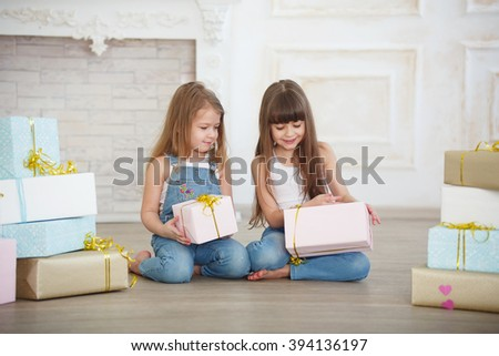 two little girls sisters give gifts - stock photo