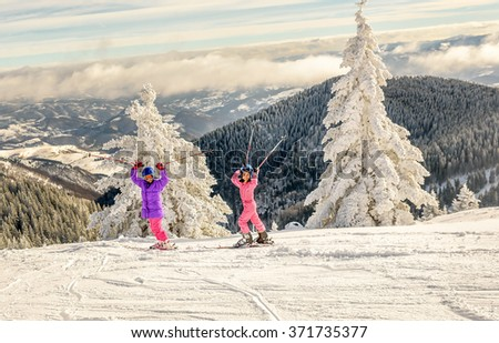 Two little girls standing with skis on the top of snowy mountain - stock photo