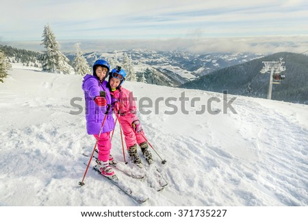 Two little girls standing with skis on the top of snowy mountain and taking a selfie with smartphone - stock photo