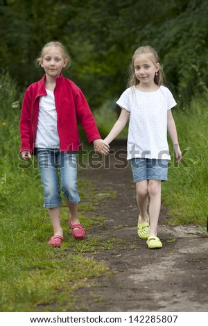 Two Little girls walking hand in hand on a path in the woods - stock photo
