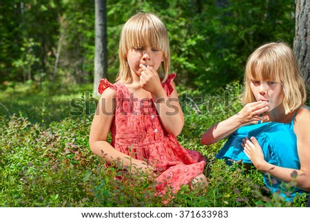 Two little girls wearing blue and red summer dress picking and eating whortleberries in a forest - stock photo