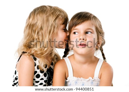 Two little girls whispering isolated over white background - stock photo