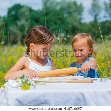 Two little girls working cookies on nature - stock photo