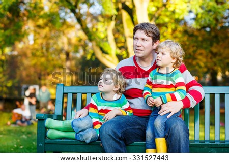 Two little kid boys and young father sitting together in colorful clothing. Funny blond siblings and their dad having fun in autumn park on warm day. Happy family of three. - stock photo