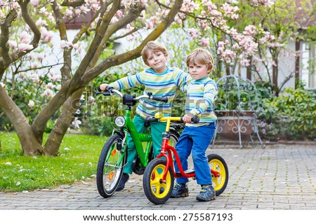 Two little kid boys biking with bicycles in park or garden on warm spring day. Active leisure for kids outdoors. - stock photo