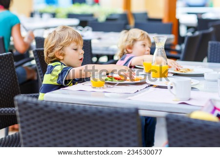 Two little kid boys having healthy breakfast in hotel restaurant or city cafe. Selective focus. - stock photo