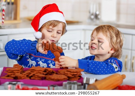 Two little kid boys in red santa hat with fresh baked gingerbread cookies. Happy about gingerbread man. Kitchen decorated for Christmas - stock photo