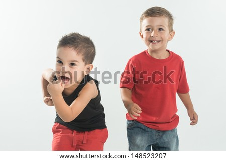 Two little kid with running gesture on white background - stock photo