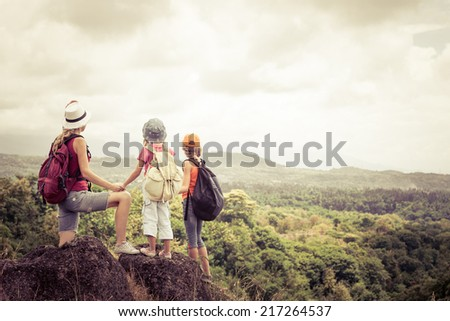 two little kids and mother standing on the mountain at the day time - stock photo