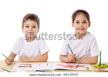 Two little kids at the table draw with watercolor, isolated on white - stock photo