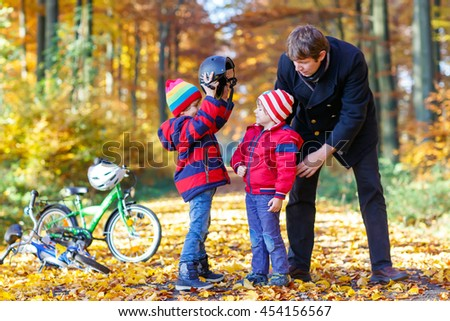 Two little kids boys and father in autumn park. Older brother and dad helping younger child to put his bike helmet. Active siblings with bicycles. Happy family - stock photo
