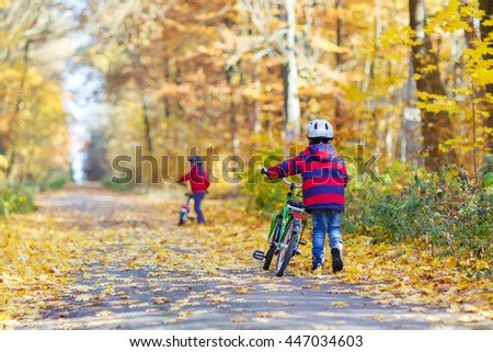 Two little kids boys, best friends in autumn forest with bikes. Active siblings, children with bicycles. - stock photo