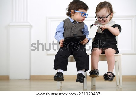 Two little kids in glasses sitting on white chairs: boy with tablet computer, girl with mobile phone - stock photo