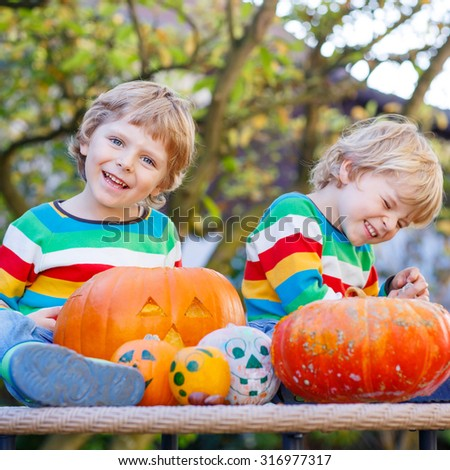 Two little kids making jack-o-lantern for halloween in autumn garden, outdoors. Happy family having fun together - stock photo
