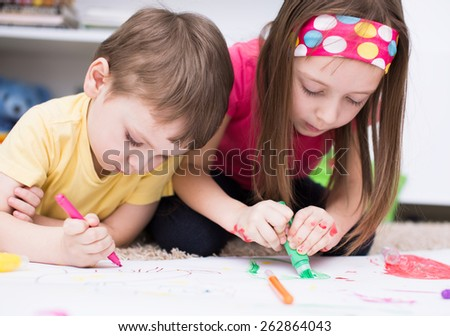 two little kids painting with paintbrush and colorful paints - stock photo