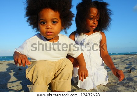 Two little kids playing in the sand - stock photo