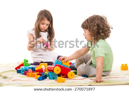 Two little kids playing with bricks home isolated on white background - stock photo