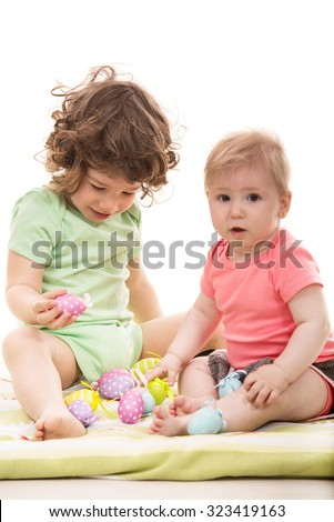 Two little kids playing with Easter eggs and sitting together on a blanket - stock photo