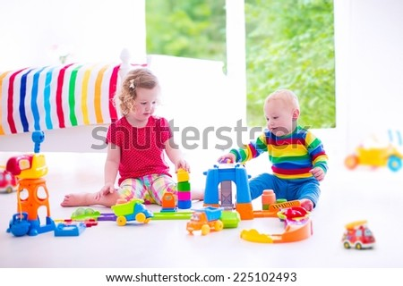 Two little kids playing with toy cars, cute curly toddler girl and a funny baby boy, brother and sister, sitting on the floor building blocks in a sunny white bedroom with big window - stock photo