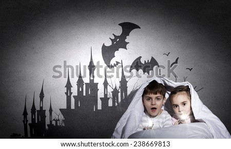 Two little kids with flashlight under blanket - stock photo