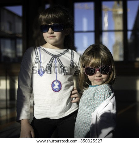 Two little models with sunglasses in a sunny day - stock photo