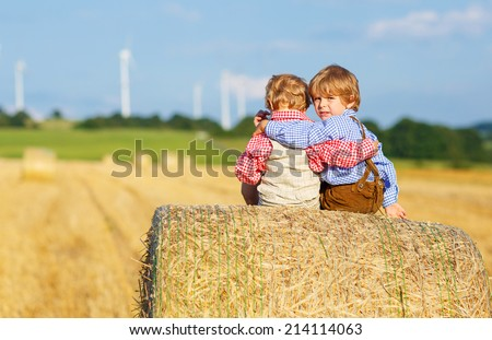 Two little sibling boys and friends in traditional German bavarian clothes sitting on hay stack or bale and speaking on yellow wheat field in summer - stock photo