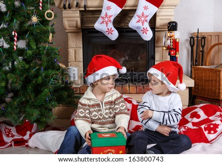 Two little sibling boys fighting about christmas present, indoor with christmas decoration - stock photo