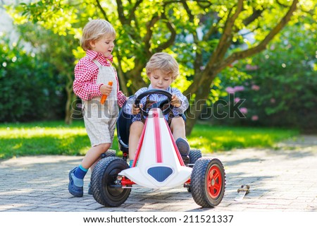 Two little sibling boys playing with pedal car in home's garden, summer, outdoors. - stock photo
