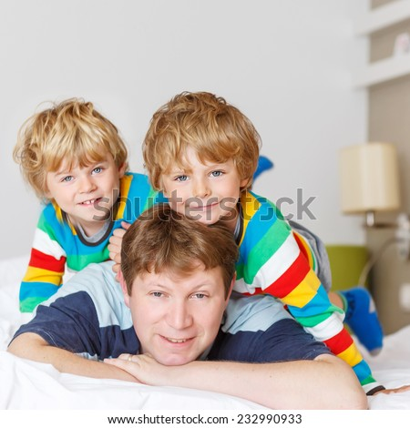 Two little sibling kid boys and their dad having fun in bed after sleeping at home, indoor. Brothers smiling at the camera. Square format. - stock photo
