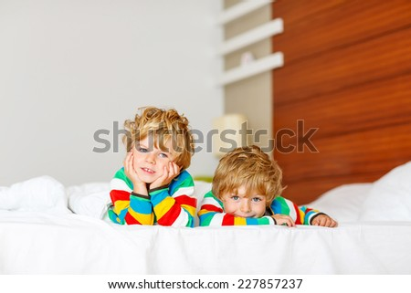 Two little sibling kid boys having fun in bed after sleeping at home, indoor. Brothers smiling at the camera. - stock photo