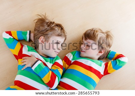 Two little sibling kid boys having fun together, indoors. Blond twins of 4 years in colorful shirts laughing and smiling. Family concept. - stock photo