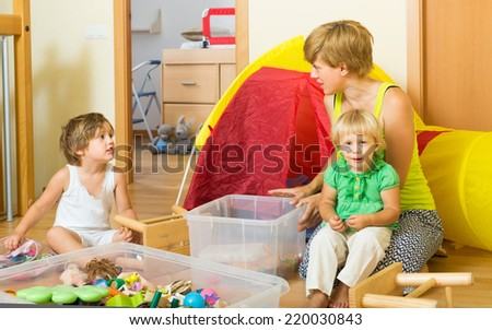Two little siblings and mother collecting toys in plastic box  - stock photo