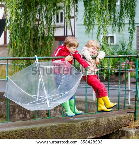 Two little siblings with big umbrella outdoors on rainy day. Kids boys having fun and wearing colorful waterproof clothes and rain boots. - stock photo