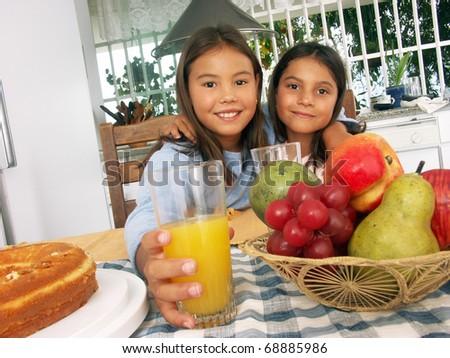 Two little sister having breakfast in a kitchen. Two little girls having breakfast at home. - stock photo