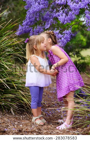 Two little sister love and have a fun in beautiful blossom garden - stock photo