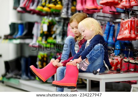 Two little sisters choosing and trying on new rain boots in a supermarket - stock photo