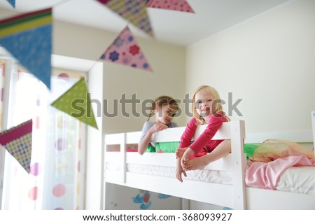 Two little sisters fooling around, playing and having fun in twin bunk bed on sunny sunday morning - stock photo