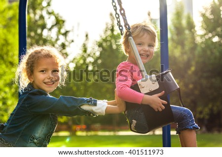 Two little sisters having fun on a swing - stock photo