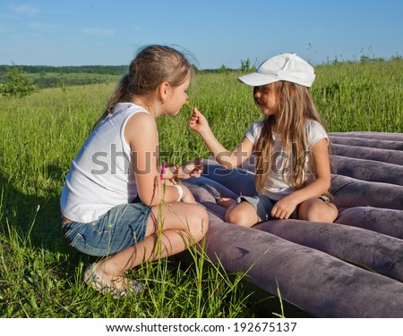 Two little sisters having fun on airbed in camping - stock photo