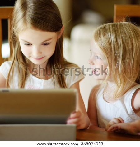 Two little sisters having fun while using digital tablet computer - stock photo