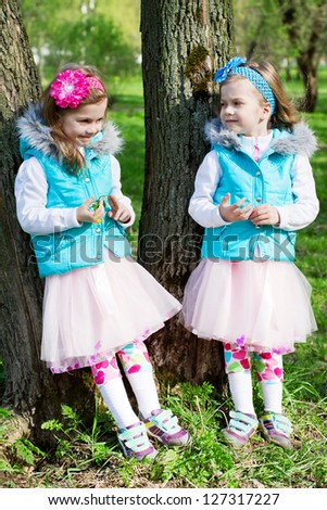 two little sisters in park in the spring - stock photo