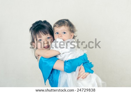 Two little sisters. Shot in studio. - stock photo