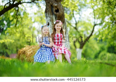 Two little sisters sitting on a haystack in apple tree garden on warm and sunny summer day - stock photo