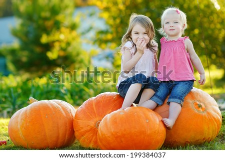 Two little sisters sitting on huge pumpkins on a pumpkin patch - stock photo