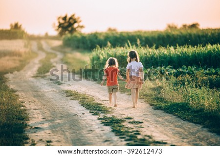 Two little sisters walking in a meadow on beautiful sunny day - stock photo